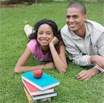 Young couple lying on grass by stack of books Stock Photo - Premium Royalty-Freenull, Code: 618-01738135
