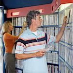 Man and woman looking for DVD's in rental shop Stock Photo - Premium Royalty-Free, Artist: Ikon Images, Code: 618-01738432