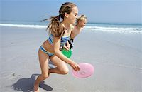 Boy and girl (11-13) running with flying disc on beach Stock Photo - Premium Royalty-Freenull, Code: 618-01738783