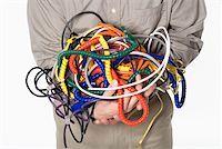 phone cord - Man holding tangled power cords Stock Photo - Premium Royalty-Freenull, Code: 604-01742081