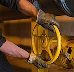 Worker wearing gloves and turning wheel Stock Photo - Premium Royalty-Free, Artist: Albert Normandin, Code: 604-01742475
