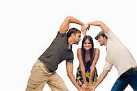 Mid adult man and a young man making a heart shape in front of a young woman Stock Photo - Premium Royalty-Freenull, Code: 625-01746335