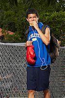 Teenage boy listening an ipod and eating empanada Stock Photo - Premium Royalty-Freenull, Code: 625-01746469