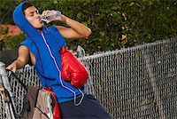 Side profile of a teenage boy listening an ipod and drinking water from a bottle Stock Photo - Premium Royalty-Freenull, Code: 625-01747720