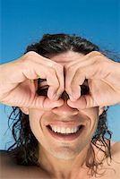 Close-up of a mid adult man making circles around his eyes with fingers Stock Photo - Premium Royalty-Freenull, Code: 625-01748142