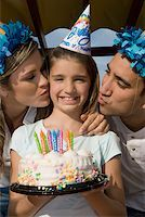 preteen kissing - Portrait of a girl holding a birthday cake and her parents kissing her Stock Photo - Premium Royalty-Freenull, Code: 625-01748253