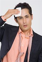 sweaty businessman - Portrait of a businessman wiping sweat with a handkerchief Stock Photo - Premium Royalty-Freenull, Code: 625-01748438