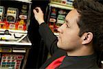 Close-up of a mid adult man playing on a slot machine Stock Photo - Premium Royalty-Freenull, Code: 625-01749128