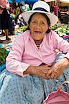 Portrait of a senior woman crouching at a market stall, Peru