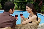 Couple sitting by swimming pool, holding wine glasses