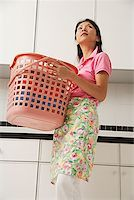 rubber apron woman - Woman doing laundry, holding laundry basket and wearing apron Stock Photo - Premium Royalty-Freenull, Code: 656-01765424