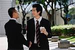 Two men wearing suits greet each other and shake hands in the park Stock Photo - Premium Royalty-Free, Artist: Asia Images, Code: 656-01766134