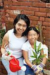 Mother and daughter, sitting in garden, holding plant and watering can