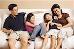 Family of four on sofa, laughing