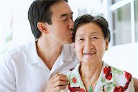 Mother and adult son together, son giving mother a kiss Stock Photo - Premium Royalty-Freenull, Code: 656-01769282
