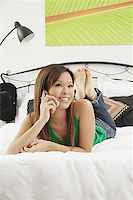 Girl in bedroom, lying on bed, using mobile phone, looking at camera Stock Photo - Premium Royalty-Freenull, Code: 656-01771222
