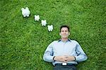 Man lying on grass, smiling, piggy banks by head Stock Photo - Premium Royalty-Free, Artist: ableimages, Code: 632-01785515
