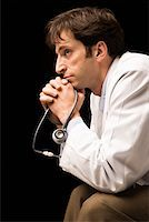 Pensive doctor with stethoscope Stock Photo - Premium Royalty-Freenull, Code: 604-01786116