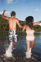Teen couple running into lake Stock Photo - Premium Royalty-Freenull, Code: 621-01799881