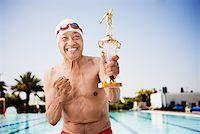seniors and swim cap - Smiling senior man swimmer holding trophy Stock Photo - Premium Royalty-Freenull, Code: 621-01800013