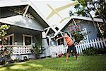 Boy flying toy airplane in front yard of house Stock Photo - Premium Royalty-Free, Artist: Ed Gifford, Code: 621-01800485