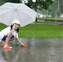 Young girl outdoors in rain playing with paper boat Stock Photo - Premium Royalty-Freenull, Code: 635-01823834