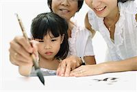 Two women and young girl indoors painting Chinese letters Stock Photo - Premium Royalty-Freenull, Code: 635-01823881
