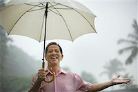 Man outdoors in rain with umbrella Stock Photo - Premium Royalty-Freenull, Code: 635-01824069