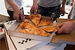 Workers taking pieces of pizza out of pizza box Stock Photo - Premium Royalty-Freenull, Code: 659-01847587