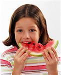 Small girl biting into a piece of watermelon Stock Photo - Premium Royalty-Freenull, Code: 659-01853275