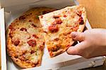 Hand taking a slice of pizza Margherita out of pizza box Stock Photo - Premium Royalty-Freenull, Code: 659-01859929