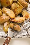 Rosemary potatoes on aluminium foil with spatula Stock Photo - Premium Royalty-Freenull, Code: 659-01864518