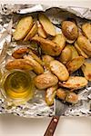 Rosemary potatoes on aluminium foil with spatula & olive oil Stock Photo - Premium Royalty-Freenull, Code: 659-01864519