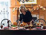 Woman serving stuffed turkey for Thanksgiving (USA) Stock Photo - Premium Royalty-Free, Artist: Cultura RM, Code: 659-01864745