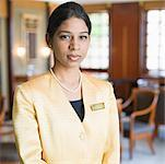 Portrait of a waitress standing in a lobby Stock Photo - Premium Royalty-Free, Artist: Glowimages, Code: 630-01873057