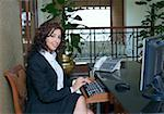 Portrait of a businesswoman working on a computer and smiling Stock Photo - Premium Royalty-Freenull, Code: 630-01873170