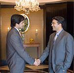 Side profile of two businessmen shaking hands and smiling in a lobby Stock Photo - Premium Royalty-Free, Artist: Visuals Unlimited, Code: 630-01873197