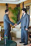 Side profile of two businessmen shaking hands and smiling in a lobby Stock Photo - Premium Royalty-Free, Artist: Visuals Unlimited, Code: 630-01873200