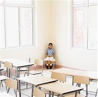 Schoolgirl sitting in the corner of a classroom Stock Photo - Premium Royalty-Freenull, Code: 630-01873577