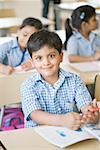 Portrait of a schoolboy sitting in a classroom and smiling Stock Photo - Premium Royalty-Freenull, Code: 630-01873779