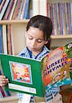 Close-up of a schoolgirl reading a book in a library Stock Photo - Premium Royalty-Freenull, Code: 630-01873797
