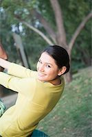 Portrait of a young woman swinging on a tire swing and smiling Stock Photo - Premium Royalty-Freenull, Code: 630-01874211