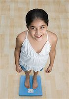 preteen  smile  one  alone - High angle view of a girl standing on a weighing scale and smiling Stock Photo - Premium Royalty-Freenull, Code: 630-01876449