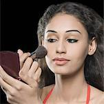 Close-up of a young woman applying blush on her face Stock Photo - Premium Royalty-Freenull, Code: 630-01876557