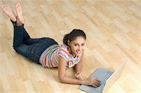 Portrait of a young woman lying on the floor and using a laptop Stock Photo - Premium Royalty-Freenull, Code: 630-01876623