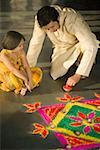 Mid adult man making a rangoli with his daughter Stock Photo - Premium Royalty-Free, Artist: Janet Bailey, Code: 630-01877200
