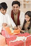 Young man sitting with his children and opening diwali gifts Stock Photo - Premium Royalty-Free, Artist: Photosindia, Code: 630-01877217