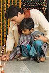 Young man lighting diwali lamps with his son Stock Photo - Premium Royalty-Free, Artist: Photosindia, Code: 630-01877226