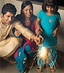 Close-up of a couple holding a sparkler with their daughter and smiling Stock Photo - Premium Royalty-Freenull, Code: 630-01877387