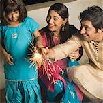 Girl with her parents burning firecrackers Stock Photo - Premium Royalty-Freenull, Code: 630-01877388